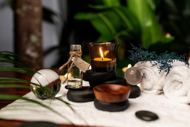 Eine brennende kerze und ein glas aromaöle stehen auf steinen zur steintherapie Premium Fotos