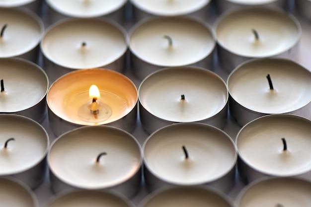 Eine brennende kerze und viele erloschene kerzen Kostenlose Fotos