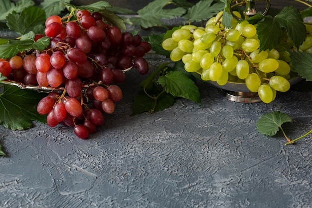 Eine bürste mit roten trauben in einem silbernen teller und eine bürste mit hellen trauben, eine rebe Premium Fotos