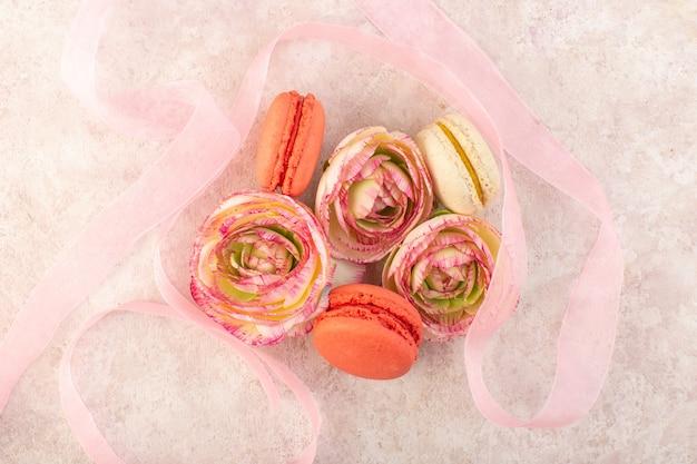 Eine bunte französische macarons der draufsicht, die mit blumen auf dem rosa schreibtischzuckerkuchenkeks lecker ist Kostenlose Fotos