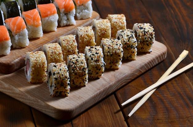 Eine detaillierte aufnahme einer reihe von japanischen sushi-rollen und ein gerät für ihre verwendung essstäbchen Premium Fotos