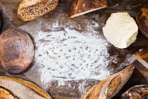 Eine draufsicht auf brot; stangenbrot und gekneteter teig mit mehl auf hölzernem schreibtisch Kostenlose Fotos