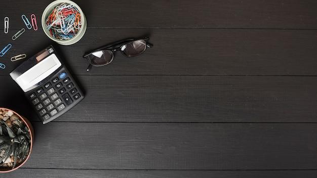 Eine draufsicht auf bunte büroklammern; rechner und brille auf schwarzem holztisch Kostenlose Fotos