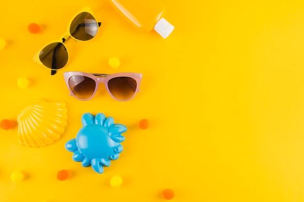 Eine draufsicht auf eine sonnenbrille; flasche mit sonnenschutzlotion; jakobsmuschel und krabben spielzeug auf gelbem hintergrund Kostenlose Fotos