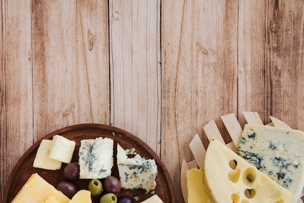 Eine draufsicht auf emmentaler; gouda und blauschimmelkäse auf achterbahn und schneidebrett Kostenlose Fotos