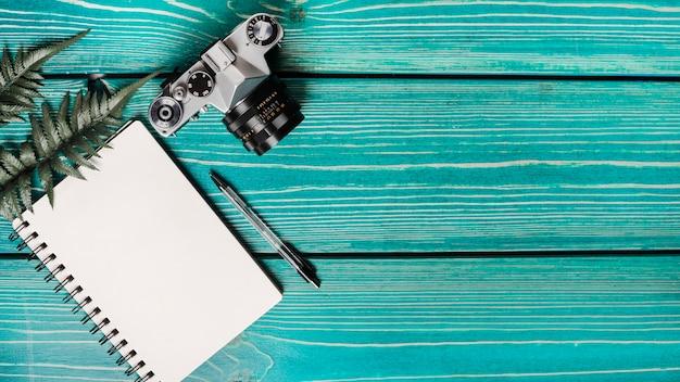 Eine draufsicht auf farnblätter; kamera; spiralblock und stift auf türkisfarbenem holzuntergrund Kostenlose Fotos