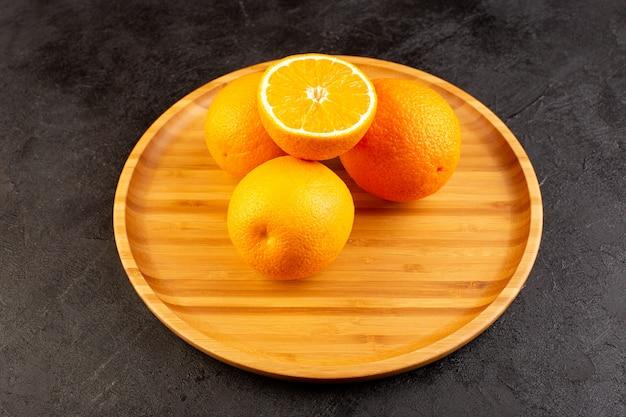 Eine draufsicht auf frische orangen sauer reif ganz und geschnittenes weiches zitrusvitamingelb auf dem dunklen schreibtisch Kostenlose Fotos