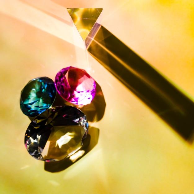 Eine draufsicht auf glänzendes rosa; grüne und gelbe diamanten auf farbigem hintergrund Kostenlose Fotos