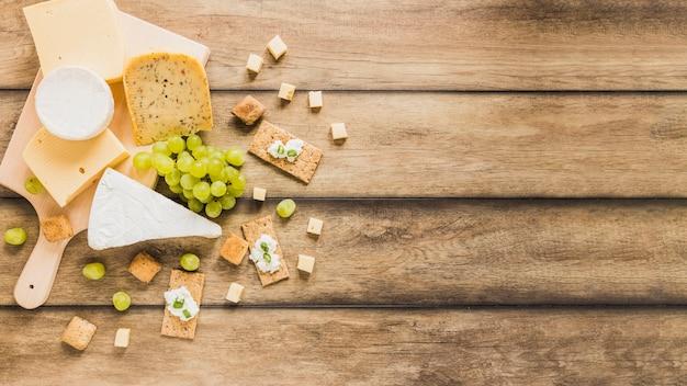 Eine draufsicht auf käseblöcke; trauben; knäckebrot mit käsecreme auf holztisch Kostenlose Fotos