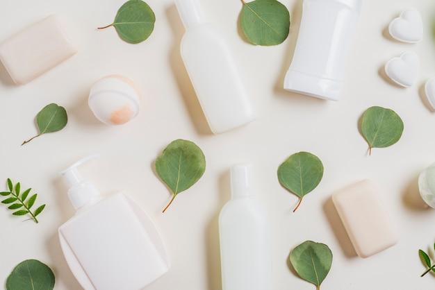 Eine draufsicht auf kosmetikprodukte; seife; badebombe und grüne blätter Kostenlose Fotos