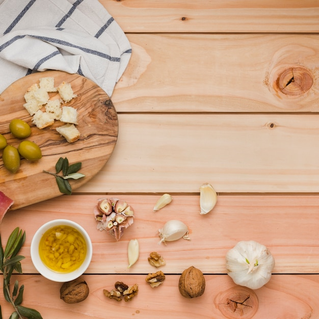 Eine draufsicht auf oliven; brot; walnüsse und hineingegossene olivenöle auf holztisch Kostenlose Fotos