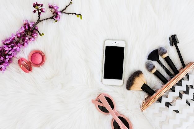 Eine draufsicht auf rosa kompakt-puder mit sonnenbrille; mobiltelefon; make-upbürste und künstlicher purpurroter zweig auf weißem pelz Kostenlose Fotos