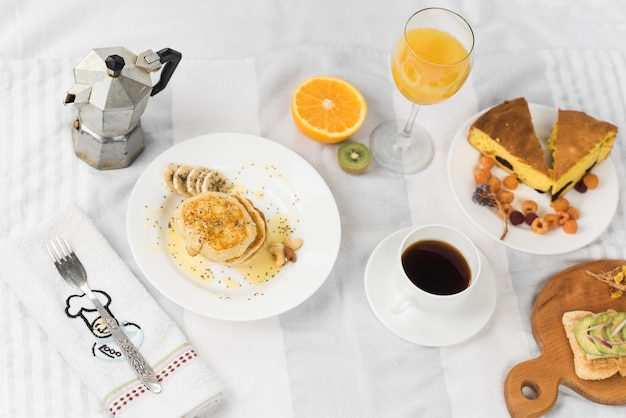 Eine draufsicht auf sandwich; pfannkuchen; saft; früchte; kaffee- und kuchenstück auf tischdecke Kostenlose Fotos