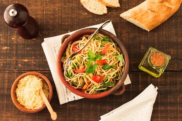 Eine draufsicht auf spaghettiteigwaren mit käse und brot auf holztisch Kostenlose Fotos