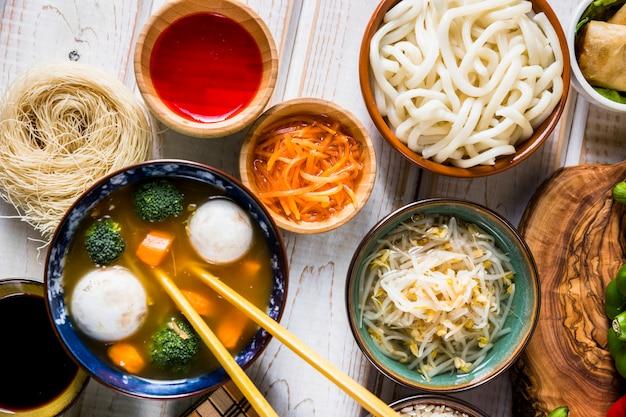 Eine draufsicht auf thailändische fisch- und gemüseschüsselsuppe mit udon-nudeln; soße und bohnensprossen auf weißem schreibtisch Kostenlose Fotos