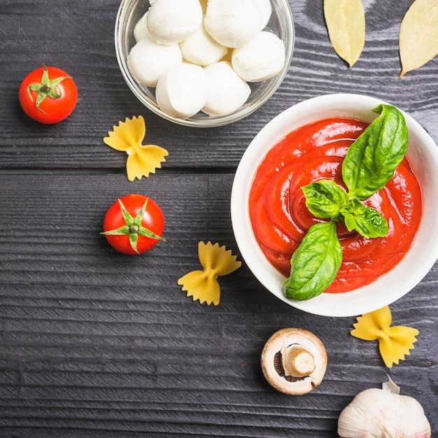 Eine draufsicht auf tomatensauce mit mozzarella; pasta; pilz und knoblauch Kostenlose Fotos