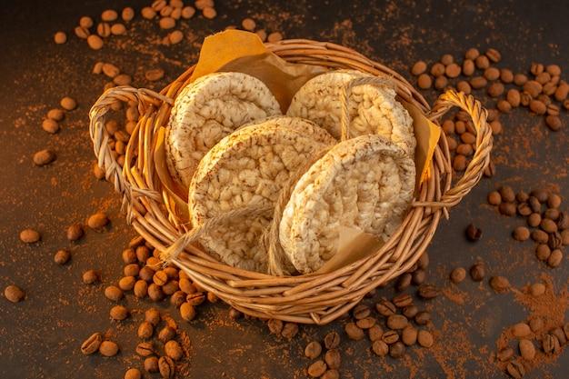 Eine draufsicht braune kaffeesamen mit korb der cracker überall auf dem braunen tisch Kostenlose Fotos