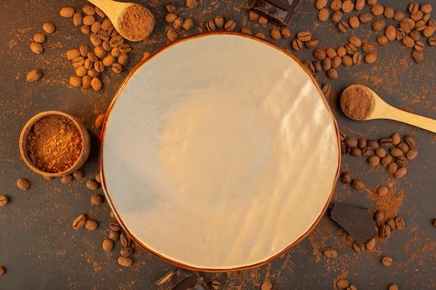 Eine draufsicht braune kaffeesamen mit schokoriegeln überall auf dem braunen hintergrundkaffee-samenkorngranulat Kostenlose Fotos