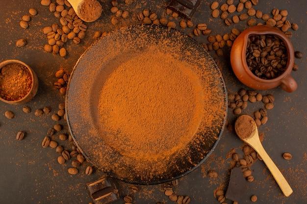 Eine draufsicht braune kaffeesamen zusammen mit schwarzem teller voll kaffeepulver mit schokoriegeln überall auf dem braunen hintergrund Kostenlose Fotos