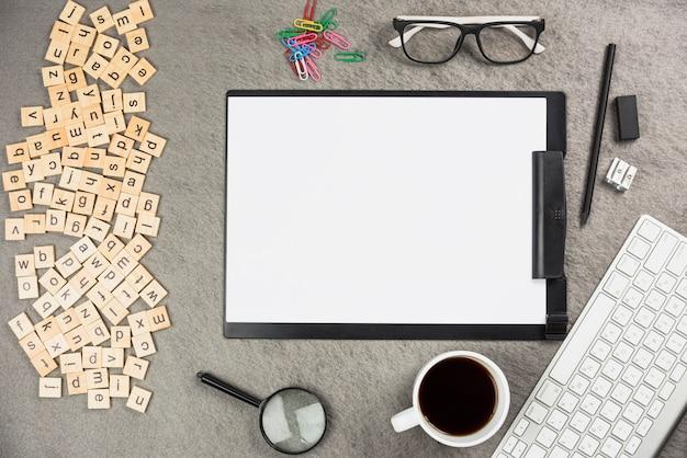 Eine draufsicht der alphabetholzkiste mit büroartikel und kaffeetasse auf schreibtisch Kostenlose Fotos