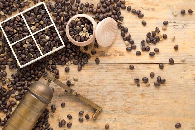 Eine draufsicht der alten kaffeemühle mit kaffeebohnen im behälter und in der tabelle Kostenlose Fotos