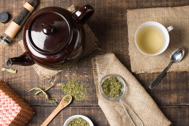 Eine draufsicht der braunen teekanne; kräuterteeschale und getrocknete teeblätter auf hölzernem schreibtisch Kostenlose Fotos