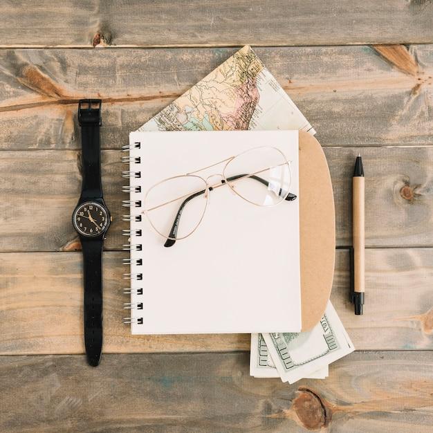 Eine draufsicht der brille auf einem spiralblock; währung; karte; armbanduhr und stift auf holzbrett hintergrund Kostenlose Fotos
