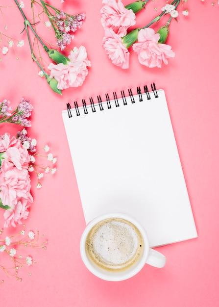 Eine draufsicht der kaffeetasse auf leerem notizblock mit nelken; gypsophila; limonium blumen auf rosa hintergrund Kostenlose Fotos