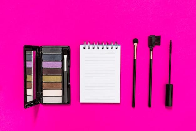 Eine draufsicht der lidschatten-palette; spiralblock und make-up-pinsel auf rosa hintergrund Kostenlose Fotos
