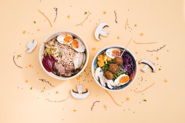 Eine draufsicht der traditionellen asiatischen kücheschüsseln, die mit pilz- und sesamkörnern auf farbigem hintergrund verziert sind Kostenlose Fotos