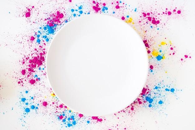 Eine draufsicht der weißen platte auf holi farbpulver über weißem hintergrund Kostenlose Fotos