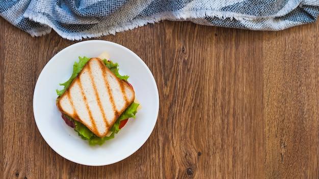 Eine draufsicht des gegrillten sandwiches auf weißer platte mit serviette Kostenlose Fotos