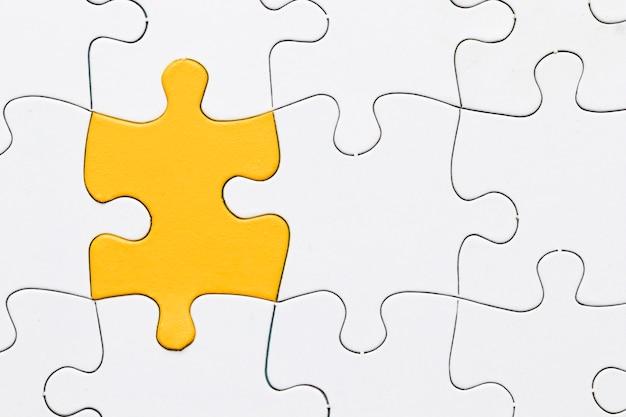 Eine draufsicht des gelben puzzlespiels unter weißem stück Kostenlose Fotos