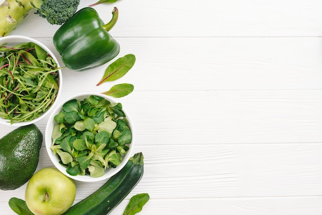 Eine draufsicht des grünen gesunden frischgemüses auf weißem hölzernem schreibtisch Kostenlose Fotos