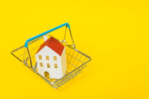 Eine draufsicht des hausmodells innerhalb des einkaufswagens gegen gelben hintergrund Kostenlose Fotos