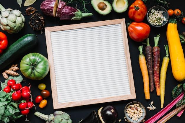 Eine draufsicht des hölzernen weißen rahmens mit buntem gemüse auf schwarzem hintergrund Kostenlose Fotos