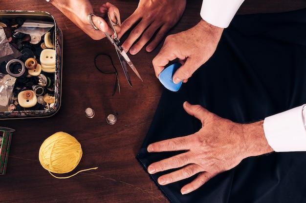 Eine draufsicht des männlichen modedesigners und seines assistenten, die in der werkstatt arbeiten Kostenlose Fotos