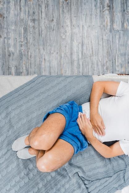 Eine draufsicht einer tragenden socke des mannes, die auf dem bett liegt, das unter magenschmerzen leiden Kostenlose Fotos