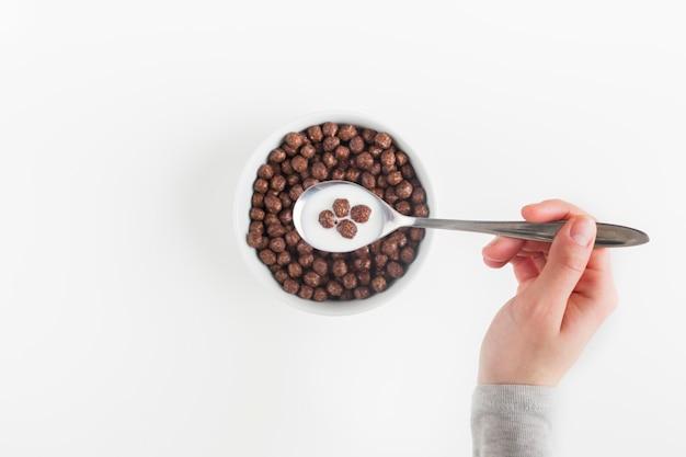 Eine draufsicht einer weiblichen hand, die löffel mit geschmackvollen getreideschokoladenbällen und -milch in der schüssel hält Kostenlose Fotos