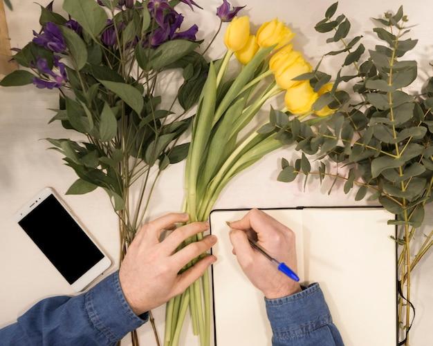 Eine draufsicht eines männlichen floristenschreibens auf tagebuch mit stift auf tabelle mit blumen Kostenlose Fotos