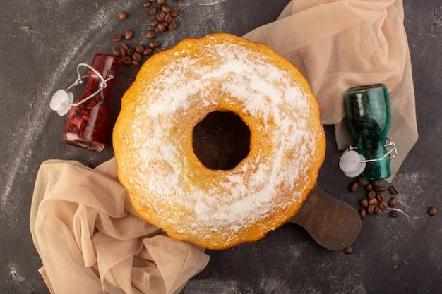Eine draufsicht gebackenen runden kuchen mit zuckerpulver und kaffeesamen auf dem hölzernen schreibtisch Kostenlose Fotos