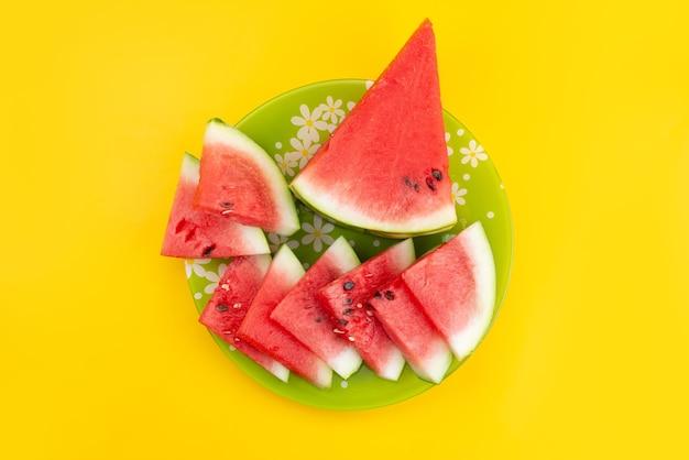 Eine draufsicht geschnittene frische wassermelone saftig und weich auf gelbem schreibtisch, fruchtsommerfarbe Kostenlose Fotos
