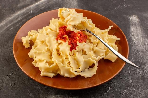 Eine draufsicht kochte italienische nudeln mit tomatensauce innerhalb der braunen platte Kostenlose Fotos