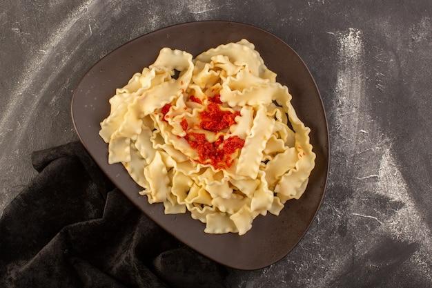 Eine draufsicht kochte italienische nudeln mit tomatensauce innerhalb platte auf dem grauen tisch essen mahlzeit italienische nudeln Kostenlose Fotos