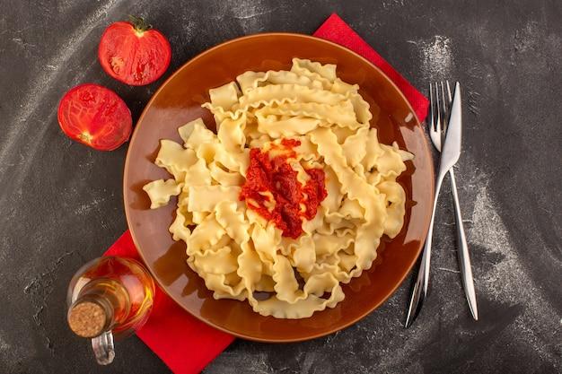 Eine draufsicht kochte italienische nudeln mit tomatensauce innerhalb platte mit besteck und tomaten Kostenlose Fotos