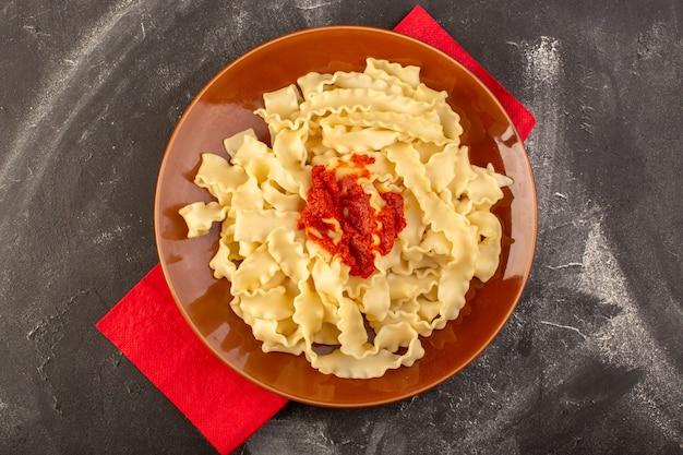 Eine draufsicht kochte italienische nudeln mit tomatensauce innerhalb platte Kostenlose Fotos