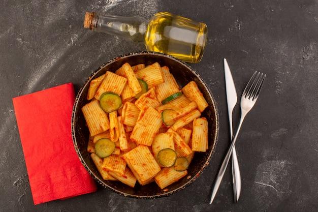 Eine draufsicht kochte italienische nudeln mit tomatensauce und gurke in der pfanne Kostenlose Fotos