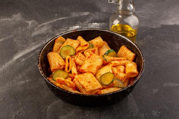 Eine draufsicht kochte italienische nudeln mit tomatensauce und gurke in pfanne auf dem dunklen tisch essen mahlzeit italienische nudelgericht Kostenlose Fotos