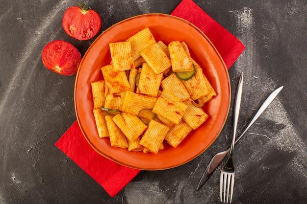 Eine draufsicht kochte italienische nudeln mit tomatensauce und gurke innerhalb platte Kostenlose Fotos