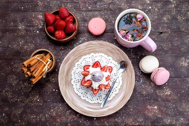 Eine draufsicht köstlicher kleiner kuchen mit sahne und frisch geschnittenen früchten zusammen mit zimt und macarons zusammen mit zimt auf dem braunen schreibtischobstkuchen Kostenlose Fotos